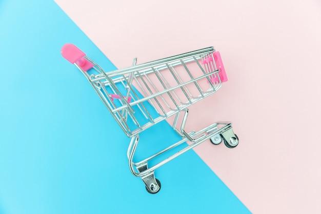 青とピンクの背景に分離されたショッピングのための小さなスーパーマーケットの食料品の押しカート
