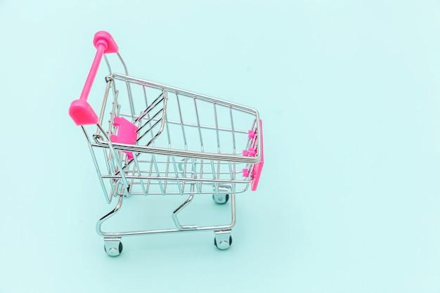 青い背景のコピースペースに分離されたショッピング用の小さなスーパーマーケットの食料品プッシュカート