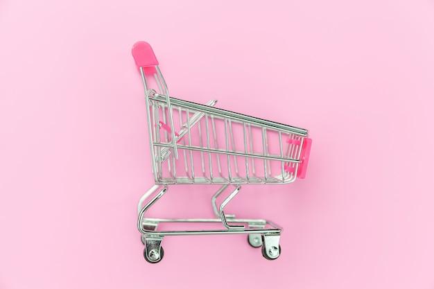 ピンクの背景に分離されたショッピングのための小さなスーパーマーケットの食料品プッシュカート