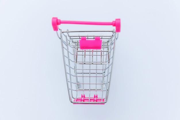 白い背景で隔離のショッピングのための小さなスーパーマーケットの食料品の押しカート
