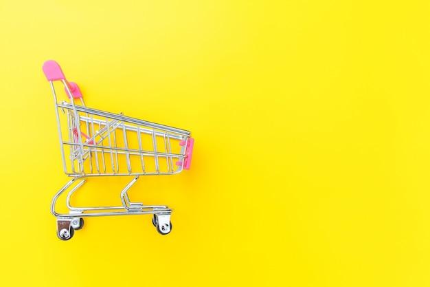 黄色の背景に分離されたショッピングのための小さなスーパーマーケットの食料品の押しカート