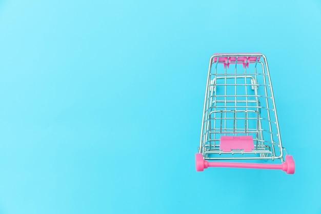 青いパステル調のカラフルなトレンディな背景コピースペースに分離された車輪付きのショッピンググッズの小さなスーパーマーケットの食料品プッシュカート。販売購入モールマーケットショップ消費者コンセプト。