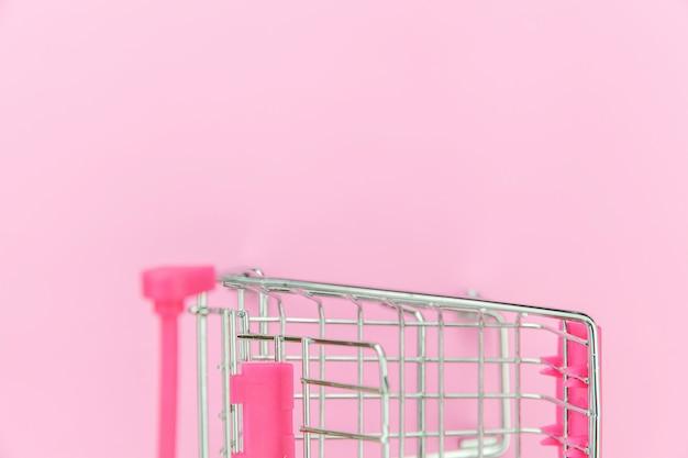 ピンクのパステル調のカラフルなトレンディな背景に分離された車輪付きのショッピンググッズの小さなスーパーマーケットの食料品の押しカート。販売購入モールマーケットショップ消費者コンセプト。コピースペース。