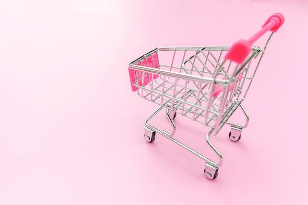 Маленькая тележка для покупок в супермаркете с колесами, изолированными на розовых пастельных красочных модных