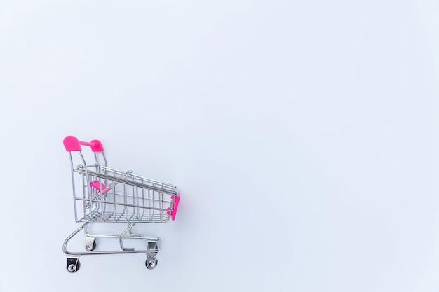 Маленькая тележка для покупок в супермаркете с колесами, изолированными на белом