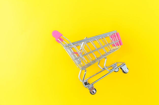 黄色のカラフルなトレンディな現代ファッションの背景に分離された車輪付きショッピンググッズの小さなスーパーマーケット食料品プッシュカート。販売購入モールマーケットショップ消費者概念。コピースペース。