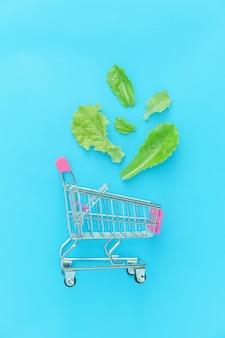 青の背景に分離された緑のレタスの葉と買い物のための小さなスーパーマーケットの食料品の押しカート