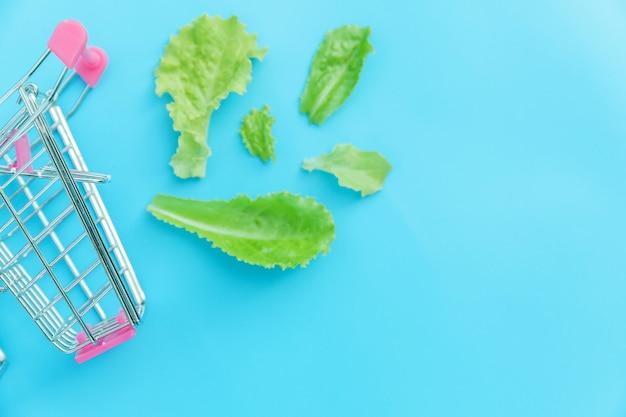 Маленькая тележка для покупок в супермаркете с зелеными листьями салата, изолированными на синем пастельном цвете