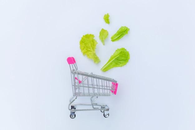 白い背景に分離された緑のレタスの葉で買い物のための小さなスーパーマーケットの食料品の押しカート