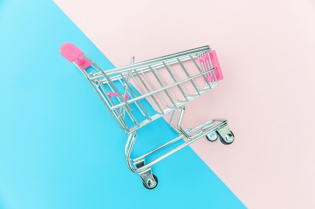 Small supermarket grocery push cart for shopping isolated on blue and pink background