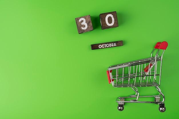 녹색 배경에 고립 된 작은 슈퍼마켓 식료품 푸시 카트 쇼핑 9 월 날짜 30 일