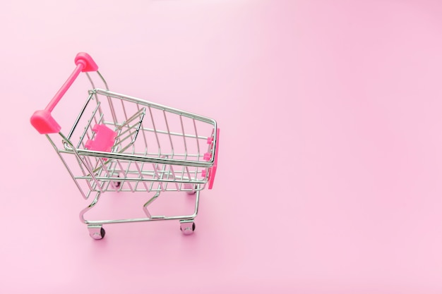 Small supermarket grocery push cart for shopping isolated on pink background