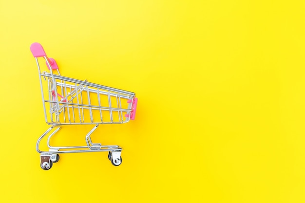 Small supermarket grocery push cart for shopping isolated on yellow background