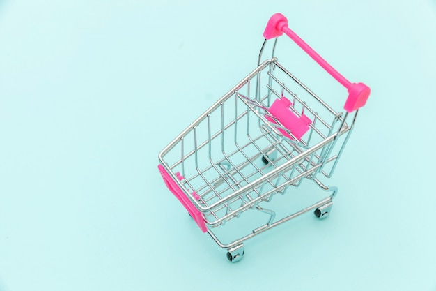 Small supermarket grocery push cart for shopping toy with wheels isolated on blue pastel colorful trendy background copy space. sale buy mall market shop consumer concept.