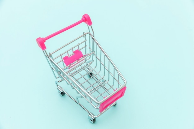 Small supermarket grocery push cart for shopping toy with wheels isolated on blue pastel colorful trendy background