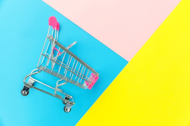 Small supermarket grocery push cart for shopping toy with wheels isolated on blue yellow pink pastel colorful trendy geometric background copy space. sale buy mall market shop consumer concept.
