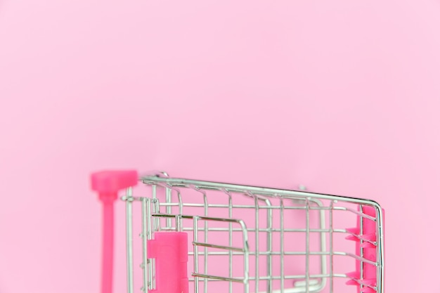 Small supermarket grocery push cart for shopping toy with wheels isolated on pink pastel colorful trendy background. sale buy mall market shop consumer concept. copy space.