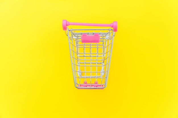 Small supermarket grocery push cart for shopping toy with wheels isolated on yellow colourful trendy modern fashion background. sale buy mall market shop consumer concept. copy space.