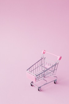 Small supermarket grocery push cart for shopping toy with wheels and pink plastic elements on pink pastel color paper flat lay background. concept of shopping. copy space for advertisement