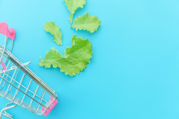 Small supermarket grocery push cart for shopping with green lettuce leaves isolated on blue background