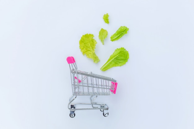 Small supermarket grocery push cart for shopping with green lettuce leaves isolated on white background