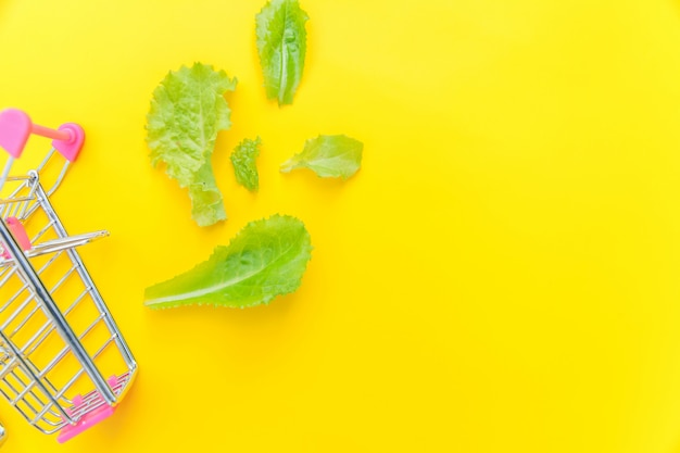 Small supermarket grocery push cart for shopping with green lettuce leaves isolated on yellow background