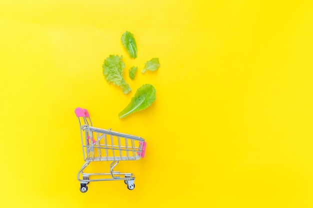 Small supermarket grocery push cart for shopping with green lettuce leaves isolated on yellow colourful trendy background