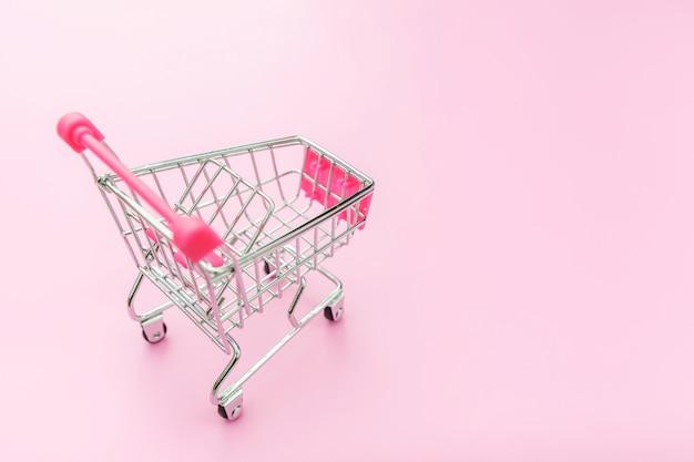 ピンクのパステルカラーのカラフルな背景に分離された小さなスーパーマーケット食料品グッズプッシュカート
