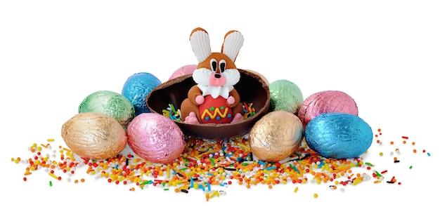 Маленький сладкий кролик и шоколадные яйца в обертке из блестящей фольги на белом фоне