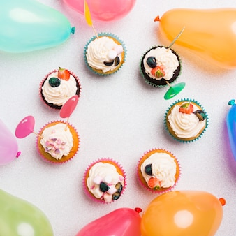 Small sweet cupcakes with air balloons on light table