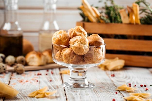 Маленький сладкий десерт профитроли в стакане