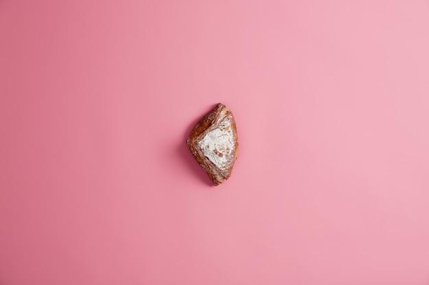 Piccolo panino al forno morbido fresco dolce scintillante di zucchero, isolato su sfondo rosa. pasticceria. delizioso dessert per colazione o cena. alimentazione malsana, cibo contenente molte calorie