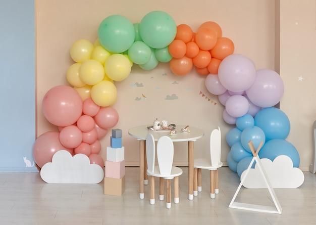 虹、カラフルなバルーンアーチと子供部屋のインテリアの小さなテーブルと椅子
