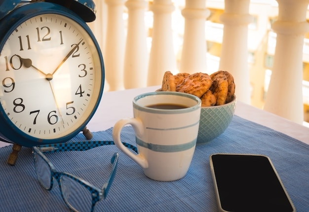 A small table outside on the balcony with a cup of coffee and some biscuits with chocolate for a break or breakfast. old blue metal alarm clock. mobile phone and eyeglasses