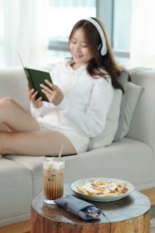 朝食に目玉焼きと冷たいコーヒーを提供する小さなテーブルとバックグラウンドで音楽を聴いたり本を読んだりする若い女性