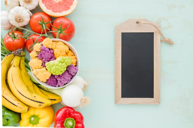 Small tag slate with healthy vegetables on colored background