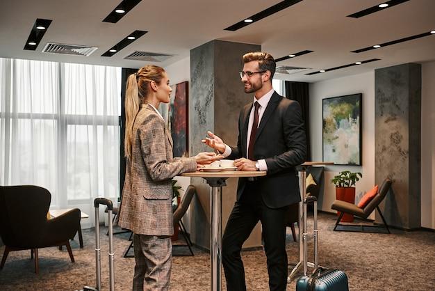 Светская беседа после подписания контракта. бизнесмен и женщина пьют кофе в холле гостиницы. женщина смеется над мужскими шутками