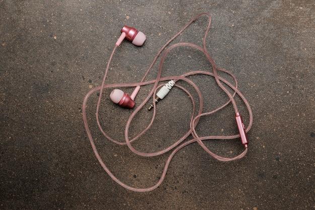 어두운 배경에 스마트폰용 작은 얽힌 분홍색 헤드폰. 평면도.