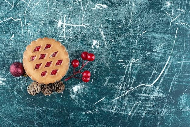クリスマスボールと松ぼっくりの小さなおいしいフルーツパイ。高品質の写真