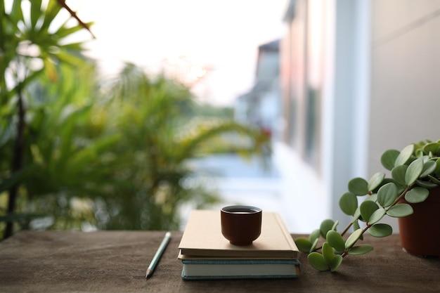 木製のテーブルに植木鉢とノートブックが付いた小さなティーカップ