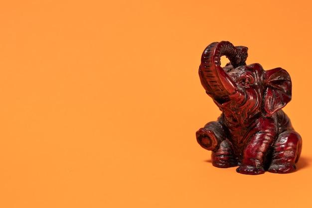 Маленькая скульптура сидящего африканского слона терракотового цвета с приподнятым хоботом.