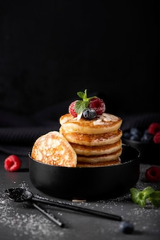 Small thin pancakes with fresh berries and honey in a black bowl, close-up
