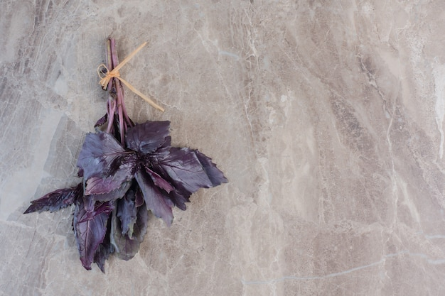 Small, tied bundle of amaranth leaves on marble.