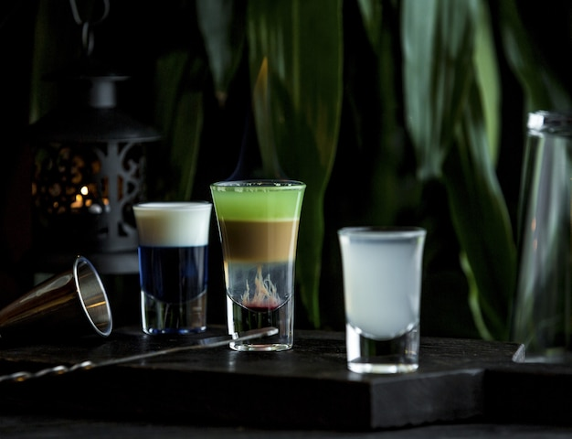 Small tiny glasses of variety of drinks in bar stand