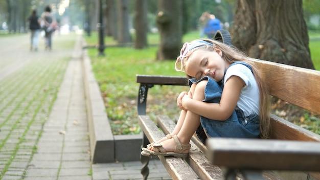 작은 피곤 소녀 여름 공원에서 쉬고 닫힌된 눈으로 벤치에 앉아.