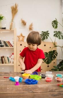 빨간 티셔츠에 작은 유아 소년은 방에있는 나무 테이블에 다채로운 플라스틱으로 재생됩니다.