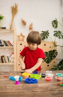 Small toddler boy in a red t-shirt plays with colorful plasticine at a wooden table in the room