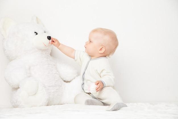 白い背景の上のテディベアの鼻に触れる白いスーツの小さな幼児。
