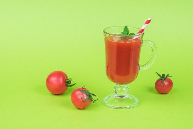緑の背景に小さなトマトとトマトジュースのガラス。
