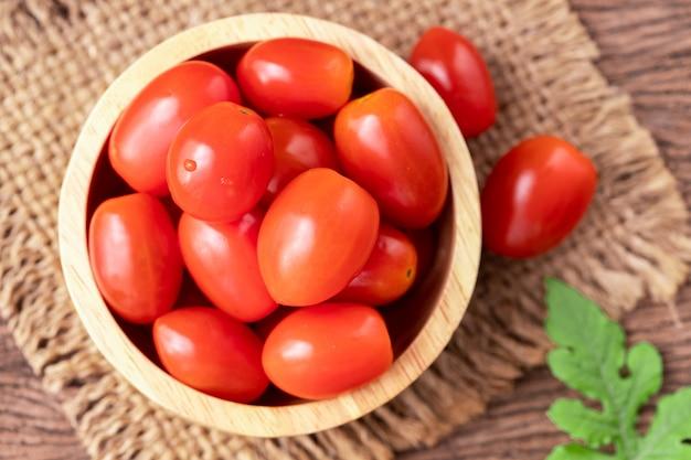 木のテーブルに小さなトマト。
